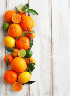 Fresh citrus fruits with leaves on wooden background by anjelagr  IFTTT 500px