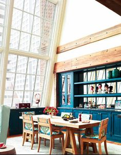 blue kitchen/glass wall... I love everything about this. the blue cabinets.. the windows and the table..