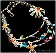The Daisys Dance Silver plated copper wire vibrant necklace, with 3 dimensional wire daisies dancing across the frame, Czech crystal and wire leaves, and amber beads at the hearts of the daisies. Easily fits an 18 inch neck and fully adjustable for comfort, carried on wire coiled snowflake obsidian segments with an extender chain. £35