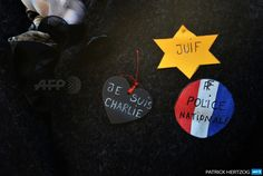 "FRANCE, Strasbourg : A woman wearing stickers reading ""Je suis Charlie"" (I am Charlie), National Police and Jewish, attends a Unity rally ""Marche Republicaine"" on January 11, 2015 in Strasbourg, eastern France, in tribute to the 17 victims of the three-day killing spree."