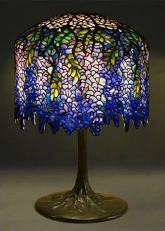 Tiffany Wisteria art nouveau style table lamp, c. Leaded glass and bronze. Wisteria Lamp, designed by Clara Driscoll. Illuminated from within by the newly invented light bulb. This lamp is shaped so that the stained glass resembles the dr Stained Glass Lamp Shades, Stained Glass Table Lamps, Tiffany Stained Glass, Tiffany Glass, Shabby Chic Lamp Shades, Rustic Lamp Shades, Art Nouveau, Cool Ideas, Tiffany Art