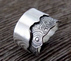 By Delias Thompson : Torn Band for Samantha Kelly .This silver band features a bold statement encompassing clean lines and torn edges. A band of heavily textured sterling embossed with roses and leaves gathers interest in it's torn edge. A second band polished to a high shine mirrors the torn edge of the first.
