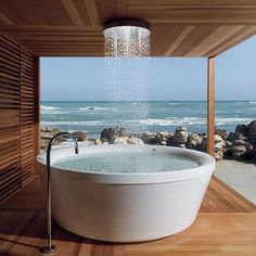 this dream set up is a reality. Designed by Italian company KOS, this gigantic soaking tub and overhead shower create a rain-like experience for the most luxurious bathrooms. I think that if I had an outdoor shower and bath like this I might never, ever leave it.