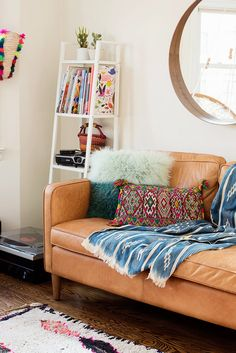 Eclectic living space with a leather sofa, a woven rug, and a mirror