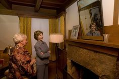 """Mrs. Laura Bush looks at a portrait of Laura Ingalls Wilder and her husband on the Wilder home mantle Oct. 3., 2008, in Mansfield, Mo. Laura Ingalls married Almanzo Wilder in the summer of 1885 and moved to the Mansfield home where the """"Little House"""" book series was written in 1894. Mrs. Jean Cody, Director and President of the Laura Ingalls Wilder Historic Home and Museum, explains that the mantle was something that the author really wanted to have. Her husband objected but obviously…"""