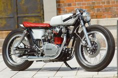 Silver Yamaha XS650 custom with twin peashooter exhaust pipes, long, narrow gas tank and red leather diamond seat by Gravel Crew