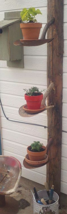 Old post + old shovel heads = rustic garden shelves.  Would look great with hanging flower baskets.