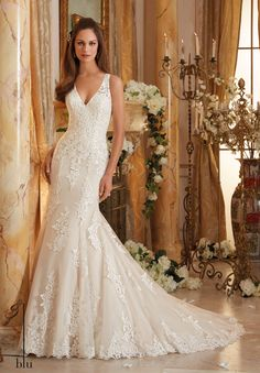 """Wedding Gowns By Blu featuring Frosted Beading on Embroidered Appliques and Wide Hemline onto Soft Net Available in Three Lengths: 55"""", 58"""", 61"""". Colors Available: White, Ivory, Ivory/Light Gold"""