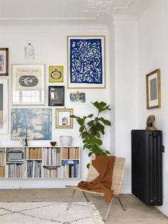 Poul Kjærjholm-stolen är en av Karens favoritfynd. Bokhyllan är designad av Karen Majs far, och säljs i parets butik. På väggen hänger en blandning av tavlor. Den lilla gröna tavlan i mitten av tavelväggen är från konstnären John Holt Iversen.