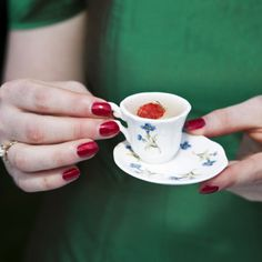 Martin Parr. interesting that the teacup is not centred on the saucer. dark red nails tie in with raspberry in teacup. green shirt makes nice background