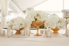 Some of the centerpieces will have gold compote vases filled white hydrangeas, white spray roses, ivory garden roses and white phalaenopsis orchids surrounded by tall votives wrapped in gold ribbon with crystal accents and gold mercury glass votives.