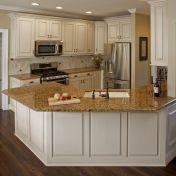 Cream kitchen cabinets and beige/brown/cream granite countertops