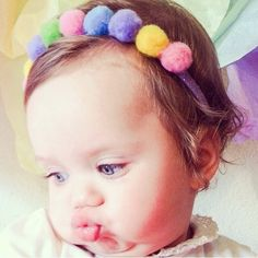 """Pom Pom Rainbow Headband handmade by Rolly Polly  Pom Pom Rainbow Headband features fun rainbow color pom poms attached to a glitter purple headband.    At check out please indicate headband size. Newborn 13"""" 0-6 months 14"""" 6-12 months 15"""" 1-3 years 16""""  4+ years 17"""""""