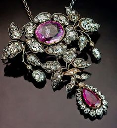 19th Century Pink Sapphire Ruby Diamond Pendant / Brooch    Of floral design, crafted in silver and 14K gold    The jewel can be worn as a pendant or a brooch.  Marked with later French import marks.  Circa 1860.