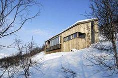 GRANKLEDD. Hytta ligger i en bratt skråning. På baksiden er det betong som tar i mot tung snø, mens fremsiden er kledd med gran.