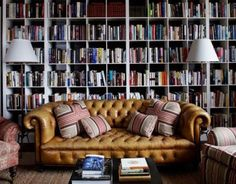 Reading room wall covered in bookshelves... Worn old chesterfield
