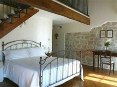 Iron bed with exposed stone wall - great look in a guest room.