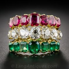 Three glorious bands wrapped around your finger in a flash of blazing technicolor. Seven rich red rubies, seven bright-white and cushion-cut diamonds and seven saturated green emeralds combine for a spectacular effect. N.B. Judging from the relative rarity of seven-stone Victorian-era rings, the artful honeycomb effect under the ring, and the seamless way in which the three shanks are sculpted to meet at the base. 7.50 carats total gemstone weight. In a ring size 8 1/2.