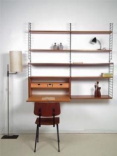Swedish design by Nisse Strinning the so called String system, designed in the 1950's. This set is in a very nice condition. The wall mounts are black and the shelves and cupboard are teak wood. The cupboard can be used as a little writing desk and has 3 drawers.