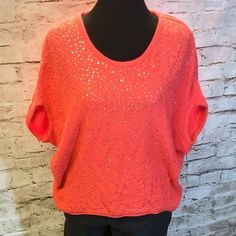 FREE PEOPLE SEQUINED SWEATER Pretty orange coral extra loose fitting sweater with sequins on the front.. Excellent condition Free People Sweaters Shrugs & Ponchos