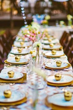 Lovely gold table setting, with golden apples, gold place mats, and a pink chevron table cloth