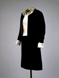 Designer: Coco Channel (French 1883-1971)  Place Made: France  Date Made: Fall-winter 1956  Medium: Wool, silk satin  Suit in black ribbed wool by Garrigue with shell blouse in ivory dot-embroidered silk satin. (Model number 04637).  Jacket is lined in the same fabric as the blouse, and the blouse's cuffs are an illusion, when the jacket is removed, a sleeveless shell is revealed.  Worn by Mrs. John F. Kennedy for a Mark Shaw photographic sitting in Georgetown, Washington, DC, 1958.