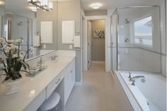 Glass shower enclosure with white bathroom vanity