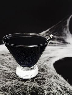 A Black Magic cocktail, black glittered Halloween or Galaxy cocktail made with black vodka, Wilton shimmer dust, orange juice, and cherry juice. With DIY for black vodka. // www.ElleTalk.com // Halloween cocktail, witch cocktail, galaxy cocktail, glitter cocktail, shimmer cocktail.