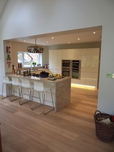 This stunning Handleless White Kitchen is perfect in this large open plan space. The extended breakfast bar gives the kitchen its entertaining quality, perfect for having guests over. By using under-plinth lighting, you achieve a luxurious finish on what is a modern masterpiece in kitchen design! We love the lampshade too :)