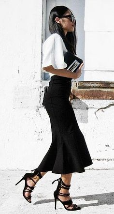 Killer black and white outfit with a fluted skirt, chic top, and lace-up heels.