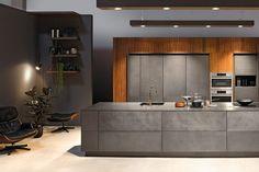 modèle de cuisine moderne en béton, parement bois, fauteuil relax en cuir et repose pieds assorti