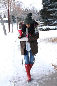winter outfit with cozy jacket and hunter boots