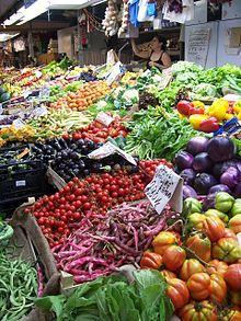 L'étal d'une marchande de fruits et légumes dans un marché couvert à Gênes.