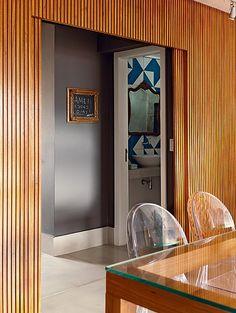 O painel ripado de freijó separa a área social da cozinha e do lavabo. Projeto da arquiteta Gabriela Marques