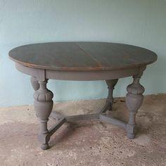 Aan deze tafel is elke maaltijd een feestje!  Prachtige echt oude ovale eettafel met geïntegreerd inklapbaar blad. De poten zijn donker matgrijs en het blad is verweerd grijs afgewerkt met een blanke beschermde lak