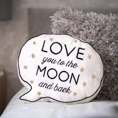 An unusal speech bubble shaped Cushion with a message saying ' Love You To The Moon and Back' embroidered in black with silver stars .