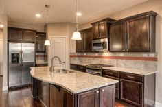 Large Lennar kitchen in the Purcell home with a corner pantry and slab granite counters with full-height backsplash.