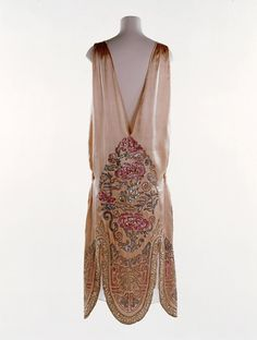 "Flapper Dress, Norman Hartnell: 1924-1926, embroidered satin. ""This... dress in a Chinese style is one of Norman Hartnell's earliest known designs. Hartnell opened his couture house in Mayfair in 1923 and rapidly gained a reputation for making exquisite evening gowns. There is a strong streak of theatricality in all his clothes and Hartnell began his design career working for the theatre. He continued to design lavish gowns for actresses to wear on and off the stage throughout his life."""