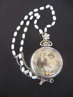 "Repurposed pocket watch case necklace I call ""Sisters"" or ""Best Friends"".  Real photo and flowers from an old lady hat."