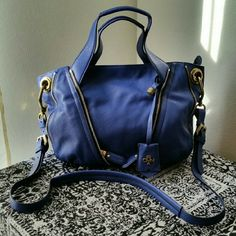 OrYANY...STUNNING AUTHENTIC LEATHER..SATCHEL ...EXCELLENT CONDITION. ...NWT ...BRAND NEW ...NO FLAWS ...STUNNING ...A MUST HAVEEEE  ...AUTHENTIC OrYANY ...100 %..GENUINE LEATHER ...true to its size and color ...color...purple blue ...gold dull studs accents   ...2 pic up close  ...zipper DECO design ...2 zipper pockets on front ...LOGO...tag ...shoulder strap included. ...zipper closing ...outside pocket ...inside zipper pockets  ...inside compartments  ...plenty of room ...measurement…