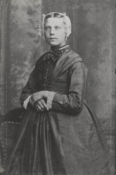 Vrouw in Vlaardingse streekdracht. De vrouw draagt een modejapon en de 'korte kap'. Onder de kap draagt ze een oorijzer met wijde gouden krullen. Aan de krullen hangen driedelige oorijzerhangers. ca 1890 #ZuidHolland #Vlaardingen
