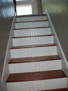 oak steps with beadboard risers. but paint the risers to match walls!