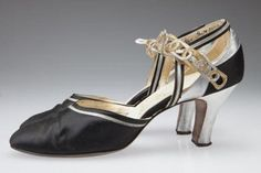 Black satin pumps with gold and silver straps, ca. 1930. Made by Beaux-Arts. Missouri History Museum collections. Women's shoes in the 1930s embodied the elegant simplicity of the era, which emphasized clean lines, subdued tones, and touches of intricate detailing. Luxurious fabrics, like the satin of these shoes, often matched the fabric of a woman's evening dress. These shoes were part of the Beaux-Arts shoe line sold by former Famous Barr Co., which nods to the French Beaux-Arts movement…
