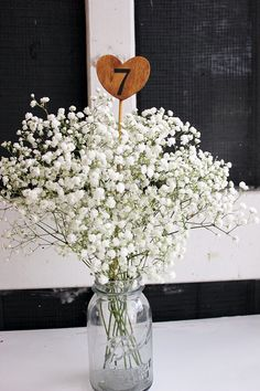 Centerpiece idea: Mason jar filled with baby's breath and wedding colours, log slice hanging on the side with table number