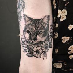Tatuagem feita por Samantha Sam de São Paulo.    Gato em realismo preto e cinza com flores ao redor do pescoço.