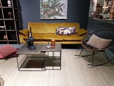 Mer innslag av Sennepsgul, med en sennepsgul soffa i et mørkt show-rom