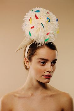 100s & 1000s | Awon Golding Millinery | Spring/Summer 2014 | This vanilla scoop is made from a soft ostrich feather pom pom and multi-coloured hand-cut coque feathers. The cone is made from woven sinamay. The piece is mounted on a sinamay covered one inch wide headband, which sits comfortably on the head