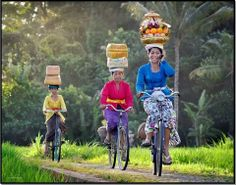 Balinese woman for celebrate Galungan day with offering on head while answer phone call Black berry