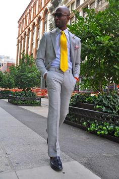 Gray suit, yellow tie, and navy tassels