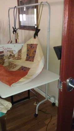 One of the ladies on my quilting forum has designed a system for holding up quilts to prevent drag when the quilt falls off the edge of the table, as any large quilt will do unless you have a HUGE …
